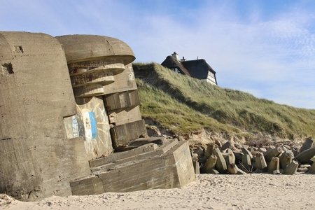 On the beach of Lokken, Denmark. Ruins of an Atlantic Wall bunker, built by the German Armed Forces in the Second World War built between 1942-1945. A house in the dunes in the background.