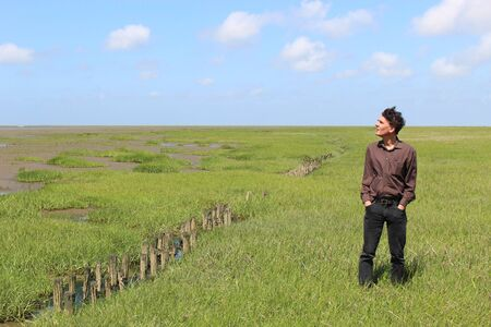 In the Wadden Sea National Park of Schleswig-Holstein. A man admires the wide landscape around him. Stock Photo