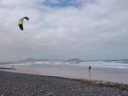 Man with a kite on Famara Beach. The wind is strong. Lanzarote, Canary Islands, Spain. Stock Photo