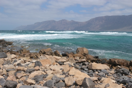 Stony beach and wild sea near Caleta de Famara, Lanzarote, Canary Islands, Spain. In the background the cliffs El Risco de Famara.