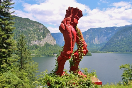 Hallstatt, Austria - June 18, 2017: Wooden sculpture on the mountain Dachstein above Hallstatt and the lake Hallstatter See. Presumably the torso represents a saltminer. The mountain was used for salt mining for centuries. Central Europe. Editorial