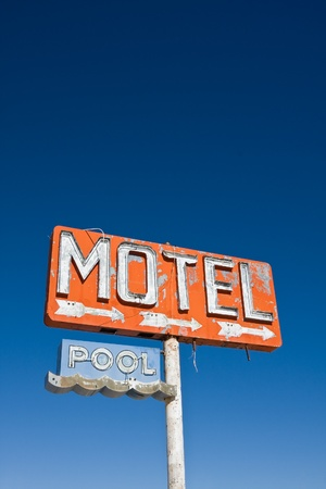 An old vintage, neon sign points to a motel that was never built.  Lots of copy space. photo