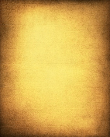 A vintage, textured golden yellow paper and cloth background with a subtle screen pattern and vignette. Stock Photo