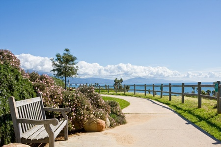 barbara: A bench and sidewalk in a public park along the coast in Santa Barbara, California. Stock Photo