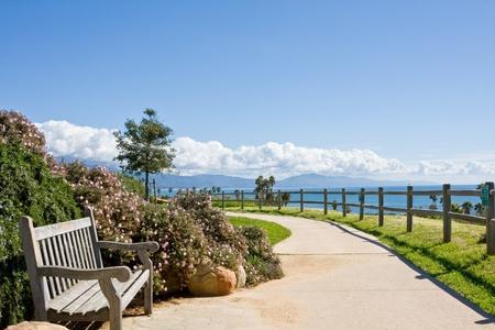 santa barbara: A bench and sidewalk in a public park along the coast in Santa Barbara, California. Stock Photo