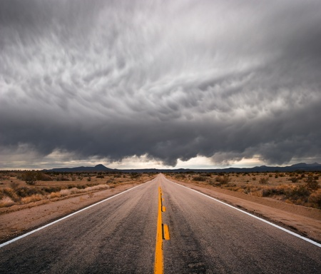 distant: An empty desert road with dark and foreboding storm clouds on the horizon.