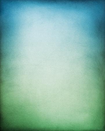 Een gestructureerd papier backgrouund met een groen naar blauw gradatie.