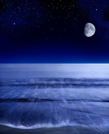 indigo: The moon glowing over a calm Pacific ocean shortly after sunset.
