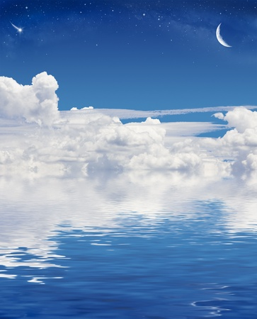 crescent: A crescent moon and shooting star above a sky of clouds reflected in a calm sea. Stock Photo