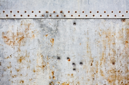 A gray metal wall background with rusted rivets and grunge stains.