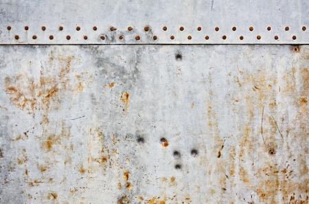 Een grijze metalen muur achtergrond met roestige nagels en grunge vlekken.