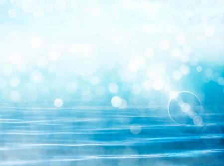 ソフト フォーカス レンズで波状の青い海の背景の上のボケ味光の効果のフレアします。