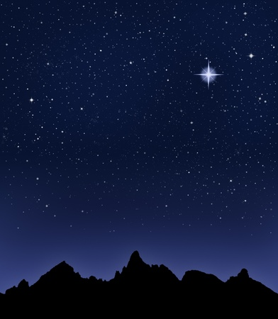 A mountain range silhouetted by a star-filled night sky.