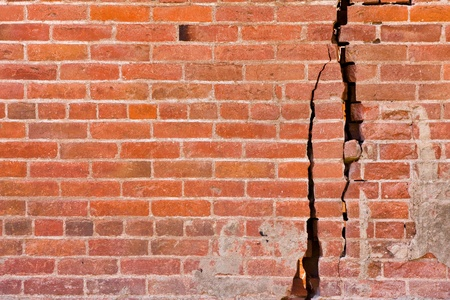 fractured: An old brick wall with major cracks and structural damage. Stock Photo