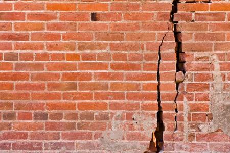 Een oude bakstenen muur met grote scheuren en structurele schade. Stockfoto