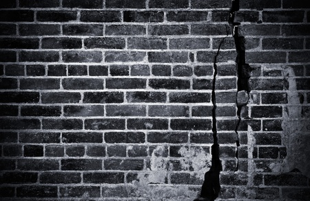 A dark and grungy brick wall with cracks and damage; done in black and white. photo