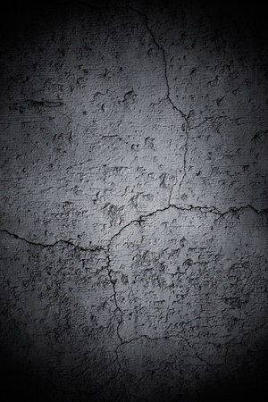 cracked cement: An old, concrete wall with cracks and a dark vignette.
