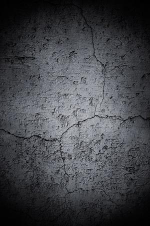 Een oude, betonnen muur met scheuren en een donkere vignet.