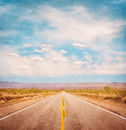 vintage: Een lege woestijnweg met een geweven achtergrond en een subtiele vignet. Stockfoto