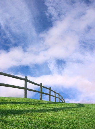 An ranch-style wooden fence with a cloudy sky background.