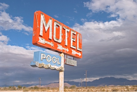 An old neon sign points to a motel complex that was never  built.  The sign overlooks an abandoned development site in Arizonas Mojave desert.
