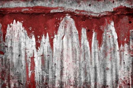 An old eroded stone wall with red drip stains. Stockfoto
