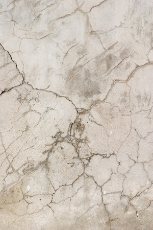 worn: An old, severely cracked concrete wall.