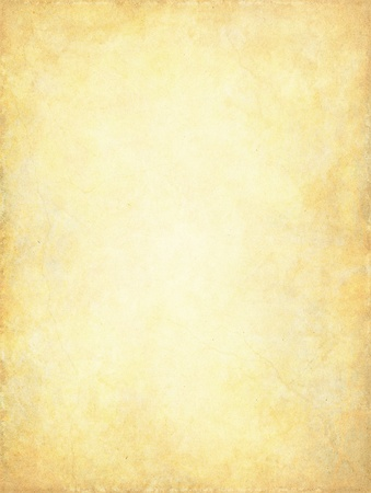 A vintage paper background with a glowing center and subtle grunge patterns and textures. Stock Photo