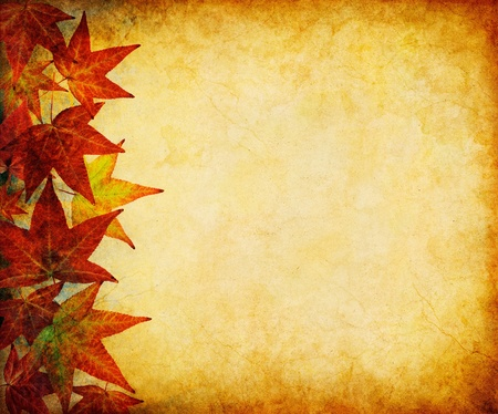 A margin of autumn leaves on a vintage, grunge paper background.