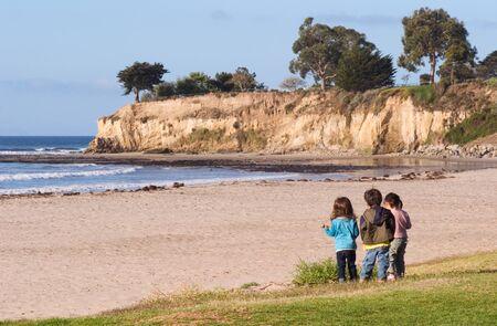 santa barbara: Three youngsters looking at the Pacific coastline and tidepools in Santa Barbara, California.