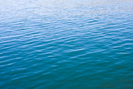 Surface water ripples with a dark to light gradation.  Stock Photo