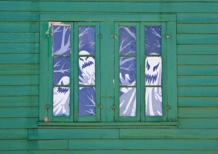 An old shed with ghost figure decorations in several windows. Stock Photo