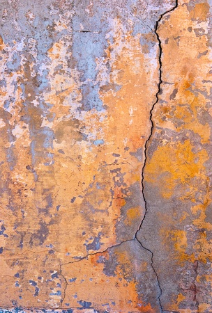 fractured: A stained and cracked old wall.