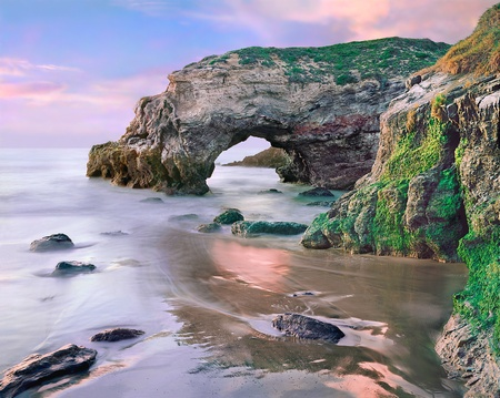 A natural arch along the Pacific coastline near Santa Barbara, California.  Image made during an extreme low tide at sunset. Stock Photo
