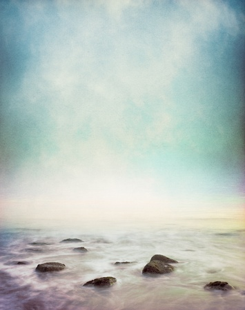 Mist and fog rising from a rocky ocean shore.  Image has a vintage paper texture and displays a pleasing grain pattern at 100%.