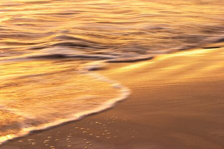 Waves and water flowing over sand at sunset.