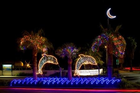 Dolphin Christmas light decorations light the entrance to Santa Barbara harbor at night. photo
