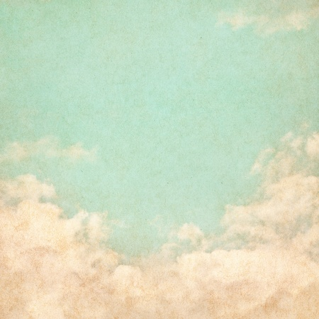 Sky, fog, and clouds on a textured vintage paper background with grunge stains.