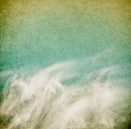 Wispy spring clouds on a textured, vintage paper background with grunge stains. photo