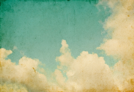 Sky and billowing clouds on a textured vintage paper background with grunge stains and retro colors  Stock Photo