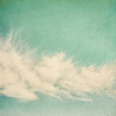 Ethereal and puffy clouds on a vintage paper background   Image has a pleasing paper grain and texture