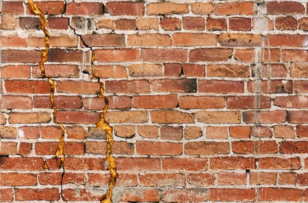 A damaged old brick wall with major cracks and splits. Stock Photo