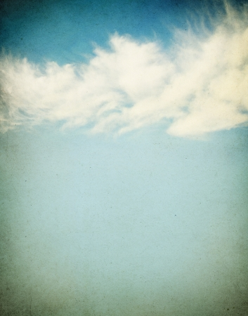 distinct: Ethereal and puffy clouds on a grunge paper background.  Image has a distinct paper grain and texture.
