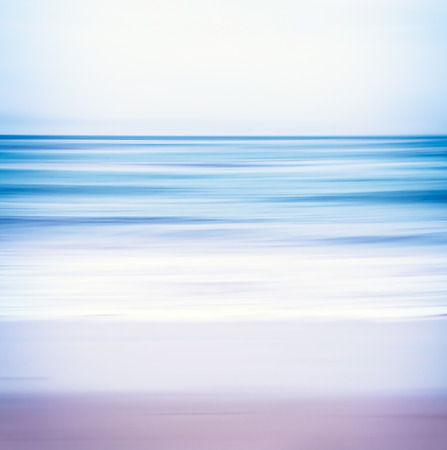 An abstract ocean seascape with blurred panning motion.  Image displays a blue and purple split-toned color scheme. Stock Photo