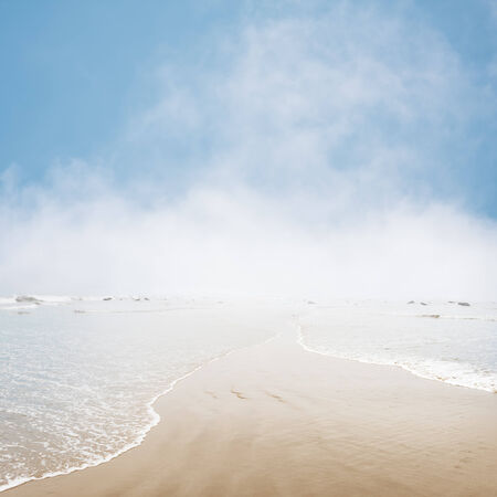Fog and mist hovering on the ocean horizon with gentle waves overlapping in the foreground. photo