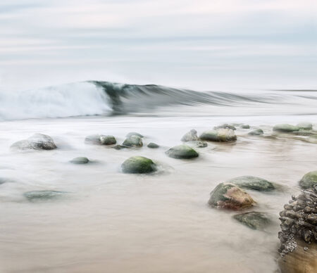 desaturated colors: A high key seascape with desaturated colors.  Image made with panning motion for a semi-blurred effect. Stock Photo