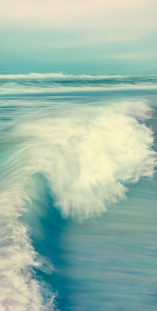 breaking wave: A breaking wave and stormy sea in a vertical panorama format.  Image made with blurred panning motion and cross-processed colors.