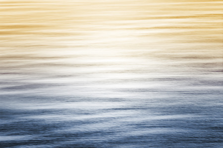Sun reflecting off of the Pacific ocean with a blue to yellow gradient.  Image made with panning motion and a long exposure for a smooth, soft focus effect.