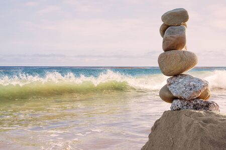 balanced rocks: A seascape featuring a column of balanced rocks and a breaking wave overlooking the Pacific ocean at sunset. Stock Photo