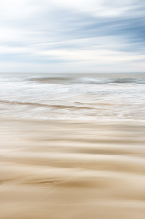 desaturated colors: A soft focus seascape with blurred panning motion combined with a long exposure.  Image displays soft, desaturated colors.